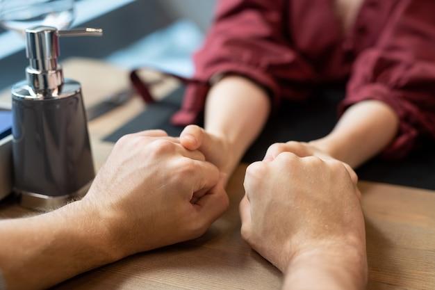 現代的なレストランやカフェで夕食時に提供されるテーブルのそばに座っている若い好色で愛情のこもった男性と女性の手