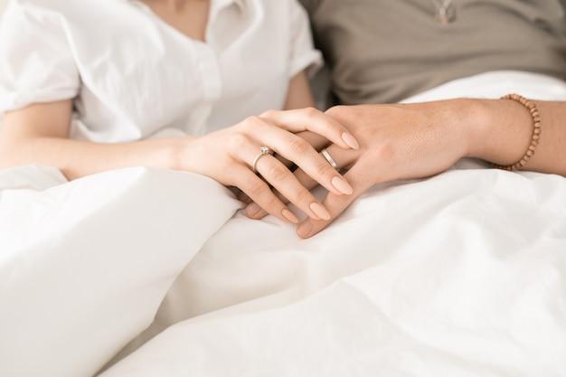 寝た後やテレビ番組を見ながら、白い毛布の下でベッドでリラックスした若い好色な夫婦の手