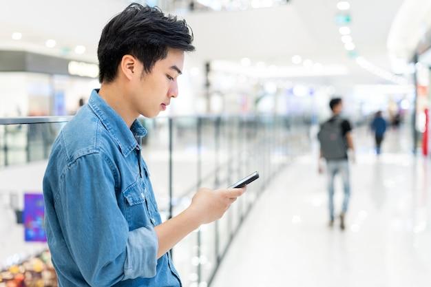 흐리게 쇼핑몰 배경에서 스마트 휴대 전화를 사용 하여 젊은 아시아 남자의 손.