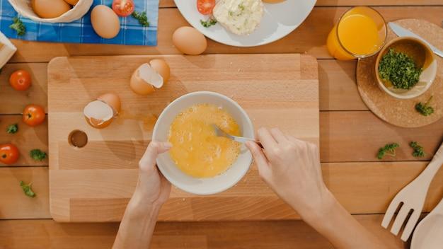 Руки молодого азиатского шеф-повара женщины взламывают яйцо в керамическую миску и готовят омлет