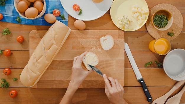 若いアジアの女性シェフの手は、木の板に全粒粉パンを切るナイフを保持します