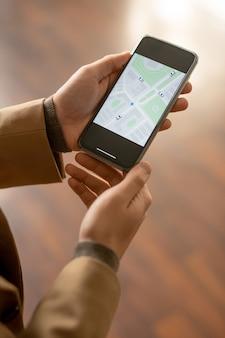 街のオンライン地図で通りや家を見つけようとしている間、携帯電話を使用してベージュのジャケットを着た青年実業家の手