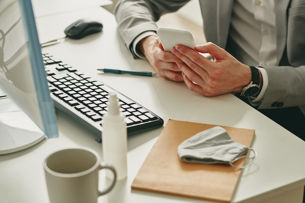 메모장, 펜, 컴퓨터 키보드 및 보호 마스크가있는 책상으로 스마트 폰을 사용하는 formalwear에서 젊은 사업가의 손