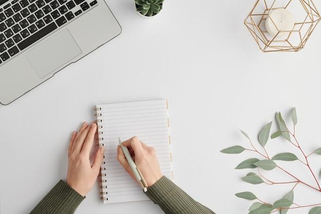 キャンドル、ラップトップ、葉の枝に囲まれたノートブックの空白のページにペンを保持している若い実業家の手