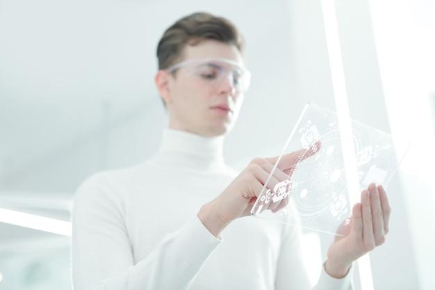 흰색 점퍼와 투명한 미래형 모바일 장치의 디스플레이를 가리키는 스마트 고글을 입은 젊은 현대 앱 개발자의 손