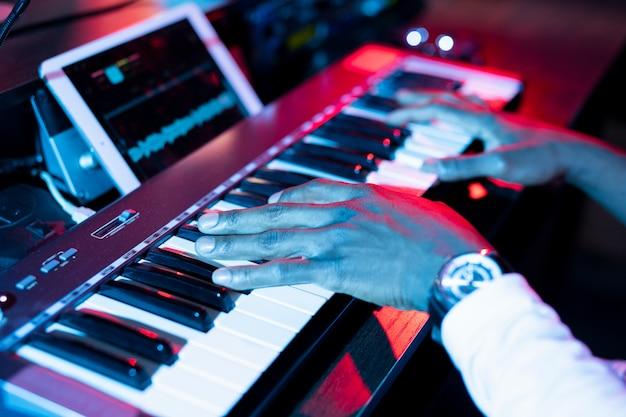 Руки молодого современного музыканта над клавишами пианино во время создания музыки и звукозаписи