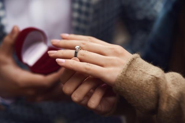 若いカップルの女の子の手は、ダイヤモンドの指輪を着ています。