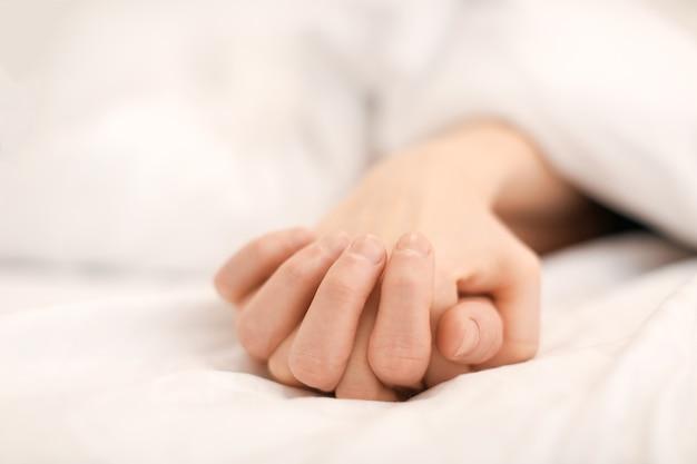 Руки молодой пары, спящей в постели