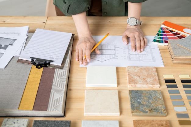 종이에 스케치로 작업하는 동안 나무 테이블에 연필 서 젊은 창조적 인 여성 디자이너 또는 건축가의 손에