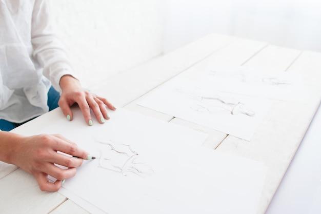 新しいコレクションを作成する若いデザイナーの手