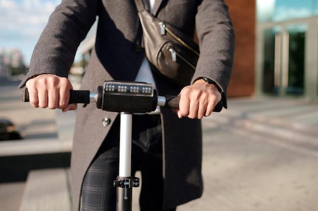 도시 환경에서 도로를 따라 이동하는 동안 전기 스쿠터의 검은 색 핸들을 잡고 코트에 젊은 우아한 사업가의 손