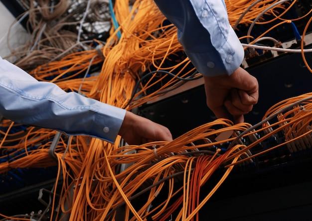 Руки молодого инженера, соединяющие кабели в серверной