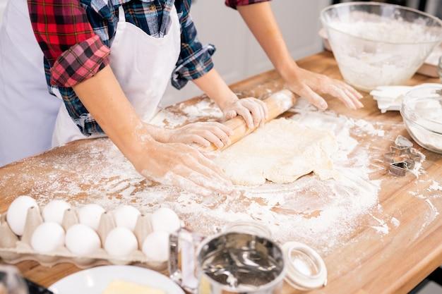 一緒にペストリーを調理しながら木製のテーブルで生地を転がすエプロンで若い女性と彼女の息子の手