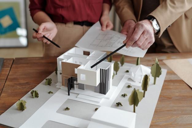 Руки молодой женщины-архитектора и ее зрелого коллеги-мужчины, указывая на модель нового дома и двора, держа бумагу с эскизом над ней