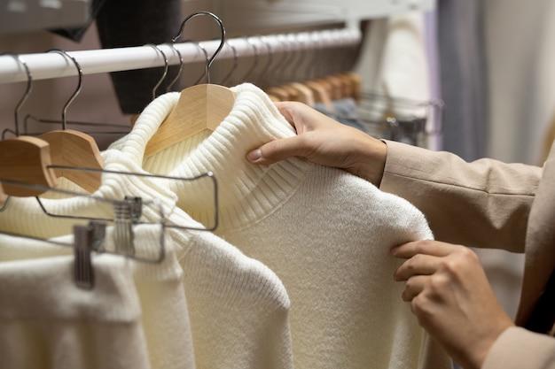 흰색 모직 스웨터가 달린 옷걸이를 들고 새로운 캐주얼 의류를 살펴보는 젊은 여성 고객의 손
