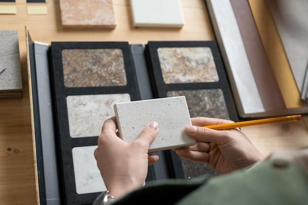 Руки молодой женщины-дизайнера, держащей образец панели над рабочим местом, изучая ее характеристики и выбирая одну для нового заказа