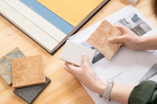 現代の家やアパートの写真と紙の上のパネルの2つのサンプルを比較するインテリアの若い女性デザイナーの手