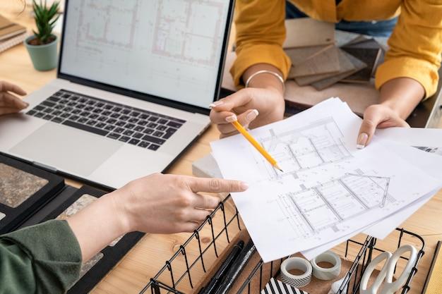 いくつかの詳細を説明しながら家のスケッチで紙を指している若い女性デザイナーや建築家の手