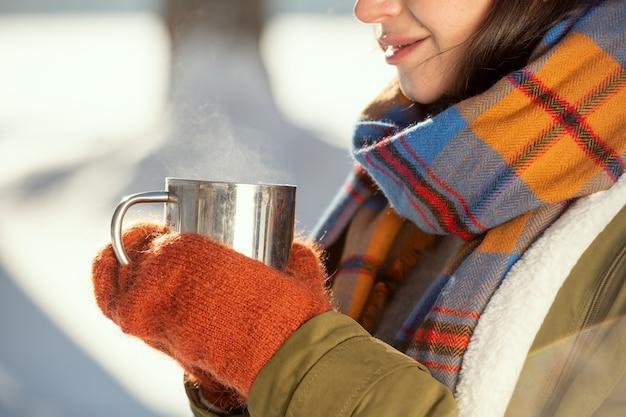 Руки молодой девушки в теплой куртке, шарфе и шерстяных вязаных варежках держат металлическую кружку с горячим чаем, стоя перед камерой