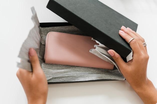 Руки молодой женщины открывают черный ящик с бежевым кожаным кошельком телесного цвета внутри, упакованный в бумагу