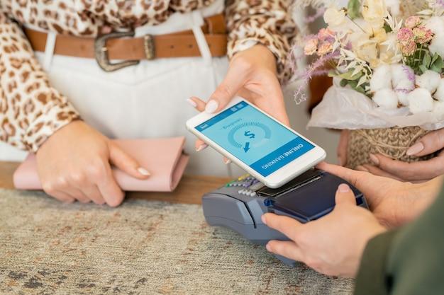 Руки молодой девушки-шопоголика с клатчем обнаженного розового цвета держат смартфон над платежным автоматом во время посещения цветочного магазина