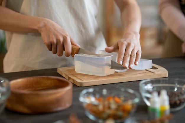 Руки молодой женщины, стоящей у стола и режущей твердую мыльную массу на деревянной доске, делая дома натуральные косметические продукты
