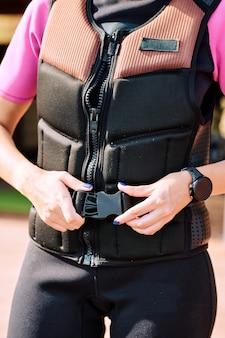 현대 여름 리조트에서 스포츠 훈련을 준비하는 동안 안전 재킷에 벨트를 고정하는 젊은 여성 서핑 보더의 손