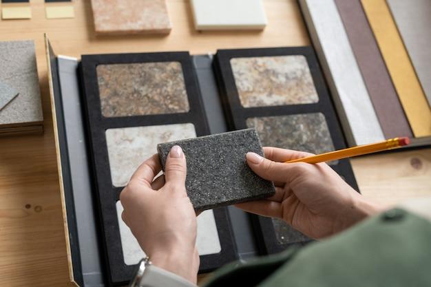 灰色の正方形の大理石のタイルを保持している鉛筆を持つ若い女性の手