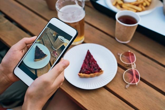 おいしいケーキの写真を撮るスマートフォンで若い女性の手