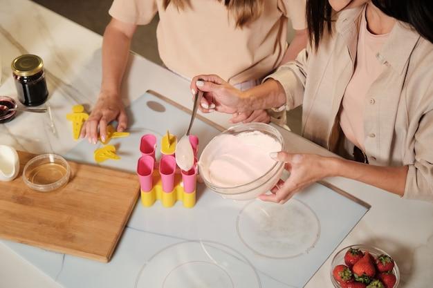 Руки молодой женщины с ложкой кладут смесь ингредиентов домашнего мороженого в силиконовые формы с дочерью, стоящей рядом
