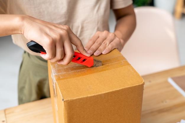 Руки молодой женщины с канцелярским ножом разрезают запечатанную клейкую ленту поверх упакованной картонной коробки, стоя у стола во время работы