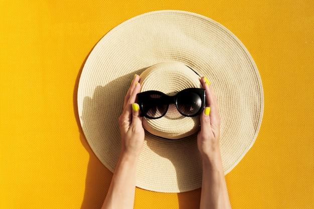 Руки молодой девушки, держащей соломенной шляпе и солнцезащитные очки на ярком желтом фоне.
