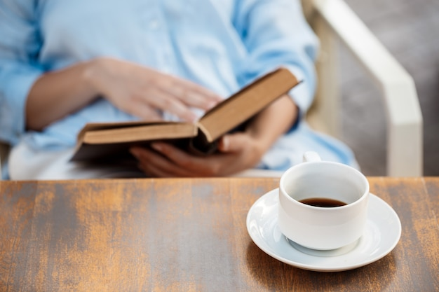 Руки маленькой девочки сидя на таблице с книгой и кофейной чашкой.