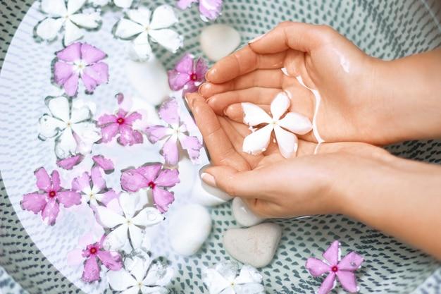 손톱에 자연 매니큐어와 물과 꽃 그릇에 젊은 여자의 손. 스파 트리트먼트와 여성 손 마사지.