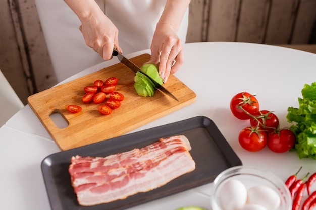 テーブルのそばに立っている間、野菜サラダのためにまな板の上で新鮮なアボカドと完熟トマトを切る若い主婦の手