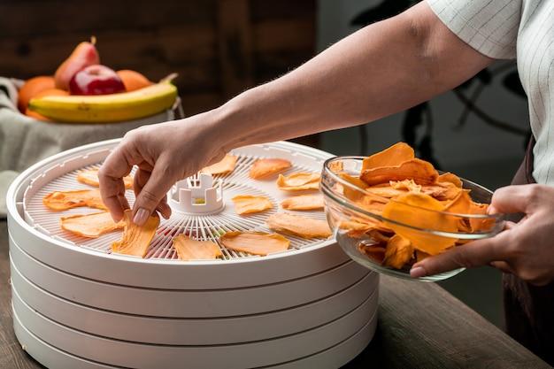 식품 건조기의 둥근 상단 트레이에서 그들을 복용하는 동안 유리 그릇에 노란색 말린 과일 조각을 넣어 젊은 주부의 손