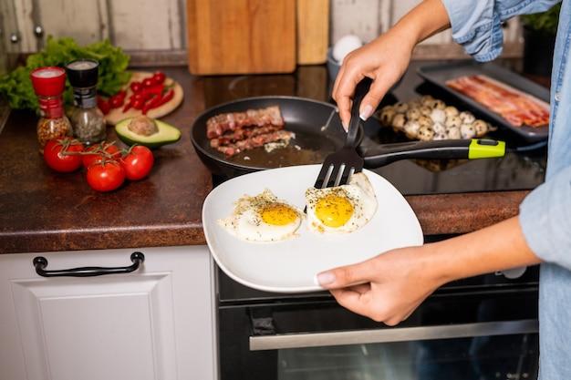 Руки молодой голодной женщины кладут яичницу на большую фарфоровую тарелку, стоя у электрической плиты на кухне перед завтраком