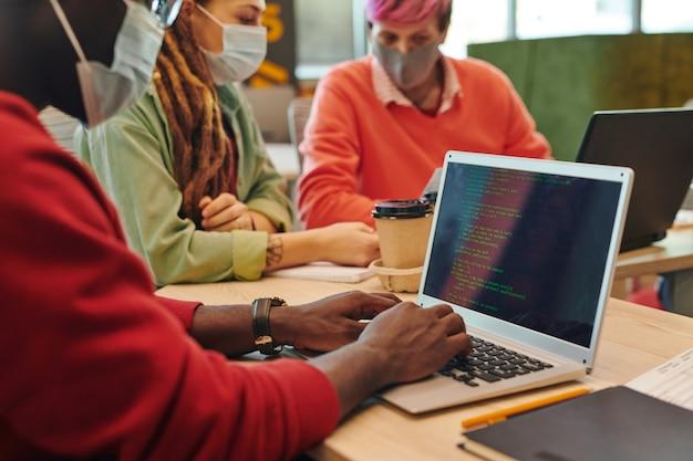 職場で新しいプログラムやソフトウェアに取り組んでいる間、ラップトップのキーパッドのキーに触れるアフリカ民族の若いitエンジニアの手
