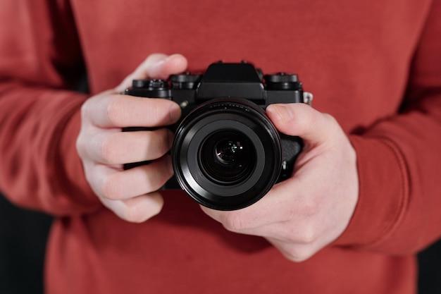 Руки молодого фотографа-мужчины в темно-бордовом свитере с новой фотокамерой на груди