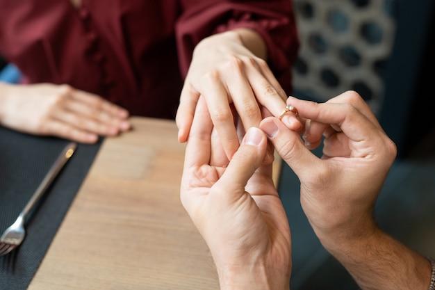 Руки молодого человека, надевающего обручальное кольцо на палец своей подруги за столом, подаваемым на ужин в современном роскошном ресторане