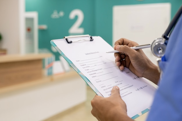 Руки молодого профессионала смешанной расы с ручкой, делающей медицинские записи в документе, работая в больнице