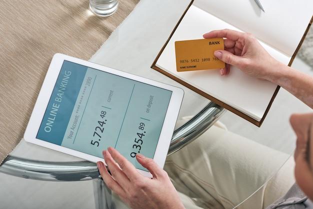 Руки молодой мобильной женщины с кредитной картой и сенсорной панелью, сидящей за столом, просматривая свой счет в онлайн-банке