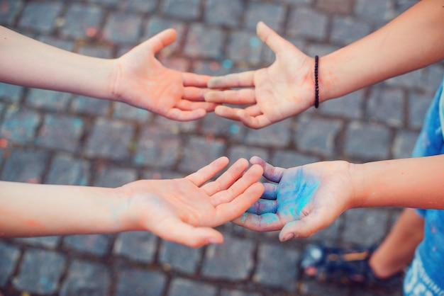 Руки молодых людей в цветах фестиваля холи, вид сверху. дети играют с красочной пудрой. празднование холи. друзья веселятся во время праздника холи. счастливое детство.