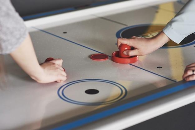 ゲームルームのエアホッケーテーブルにストライカーを保持している若者の手