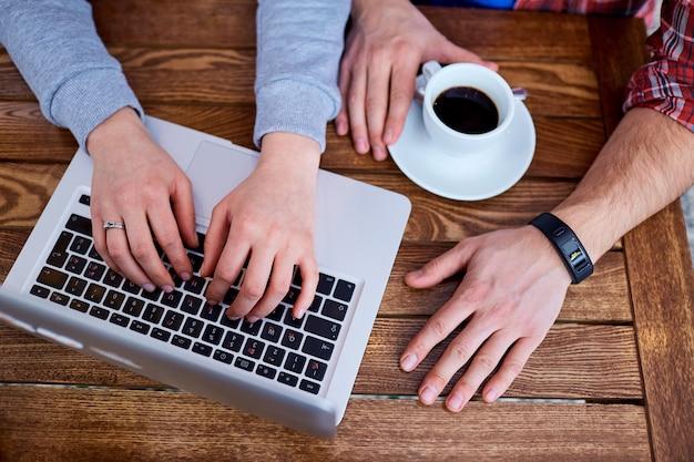 컵 커피 클로즈업으로 카페에서 노트북에 입력하는 젊은 사람들의 손에.