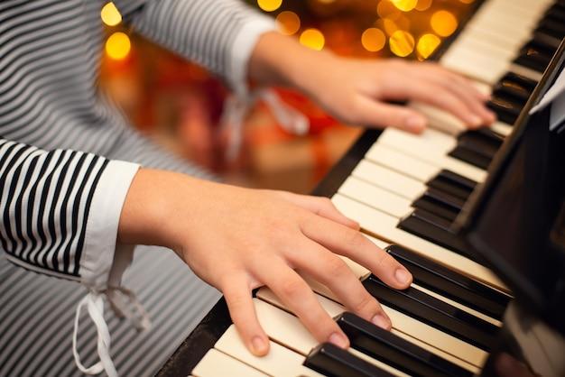 피아노에 젊은 피아니스트의 손을 닫고 배경에 크리스마스 조명. 겨울 휴가 장식 및 음악의 개념입니다.
