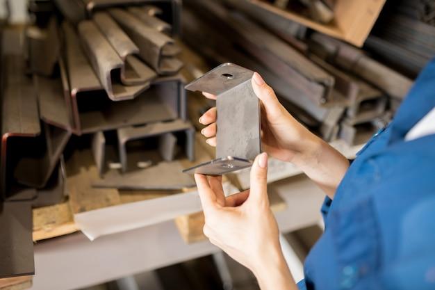 Руки молодого профессионального промышленного техника, держащего новую металлическую или стальную запчасть, выбирая одну для ремонта машины