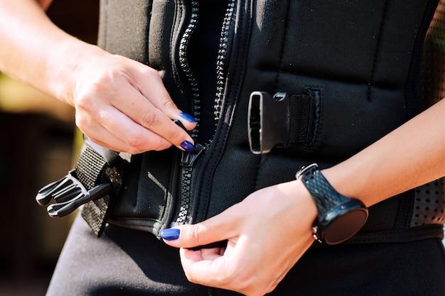 서퍼를 위한 현대 여름 휴양지에서 스포츠 훈련을 준비하는 동안 안전 재킷을 지퍼로 잠그는 젊은 스포츠 여성의 손