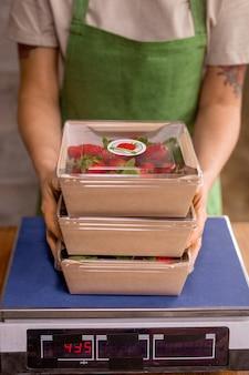 梱包後にはかりにそれらを置きながら、新鮮な熟したイチゴとコンテナのスタックを保持している若い垂直農法労働者の手