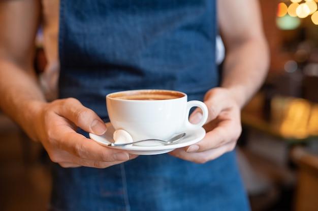 Руки молодого официанта стильного ресторана несут чашку свежего капучино с ложкой и крошечным безе на блюдце